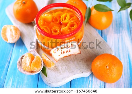 Orange jam with zest and tangerines, on blue wooden table