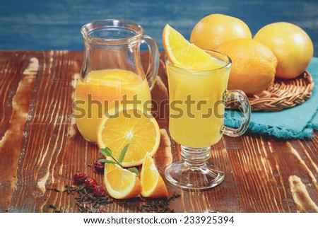 Orange juice and fresh oranges over rustic background. A macro photograph with very shallow depth of field. Done with vintage retro filter. - stock photo