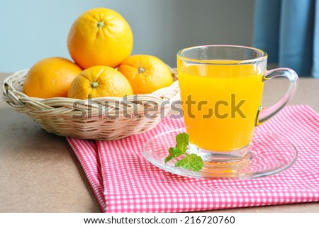 Orange juice and oranges in basket on wooden table. - stock photo