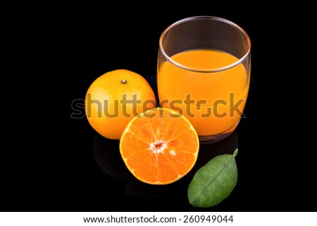 orange juice and slice isolated on black background, Fruits of a ripe orange and juice in a glass on a black background - stock photo