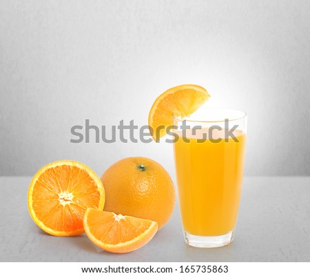 Orange juice and slices on a gray background