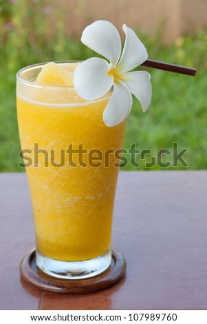 Orange juice blender in a glass and white flower - stock photo