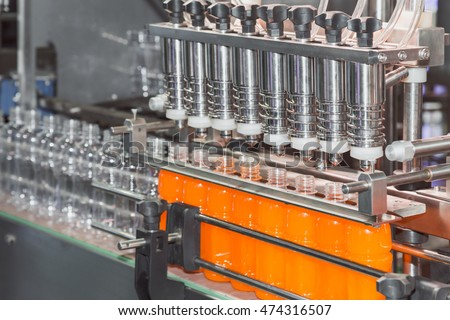 orange juice bottle on factory line machine in the factory, orange bottles transfer on conveyor belt system