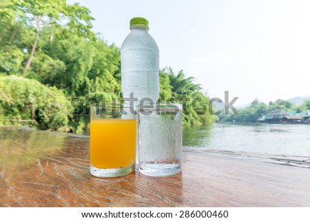 Orange juice glass ,cold mineral water and Soda water bottle  on the table of the natural background - stock photo