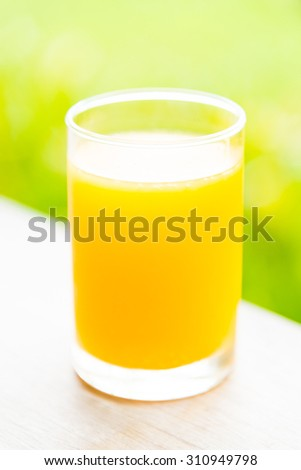 Orange juice glass with outdoor view background