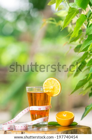 orange juice healthy fruit and tape measure placed on the table in the morning. - stock photo