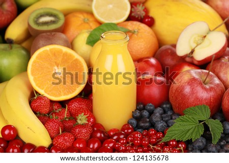 Orange juice in a bottle surrounded by fresh fruits - stock photo