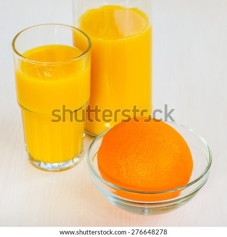 Orange juice in a glass bottle and glass on a white background