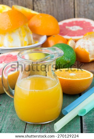 Orange juice in a jug and citrus on the table. Soft focus
