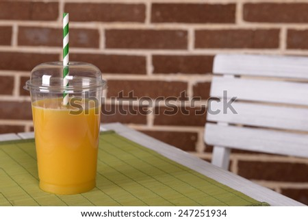 Orange juice in fast food closed cup with tube on wooden table and brick wall background - stock photo