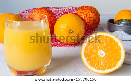 Orange juice in glass and orange on wooden table