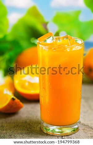 Orange juice in glass, fresh cold drink with ice - stock photo