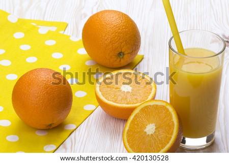 Orange juice in glass,  fresh fruits on light wooden background - stock photo