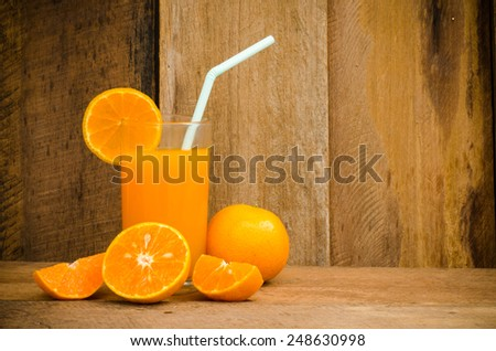 Orange juice in glass , fresh fruits on wooden background - stock photo