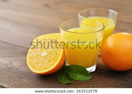 Orange juice in glass with  fresh fruits on wooden background - stock photo