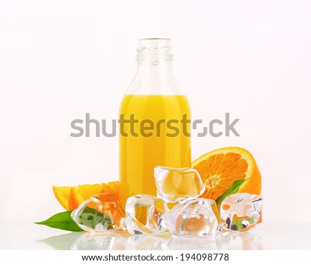 orange juice in the glass bottle, accompanied with fresh oranges and ice cubes - stock photo