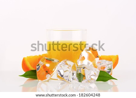 orange juice in the glass, surrounded with ice cubes and fresh oranges with leaves - stock photo