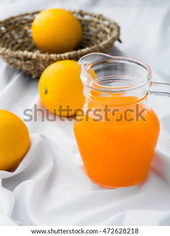 orange juice on crumpled white cloth background