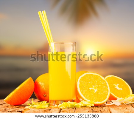 Orange juice on wooden table, summer drink with sunset background - stock photo