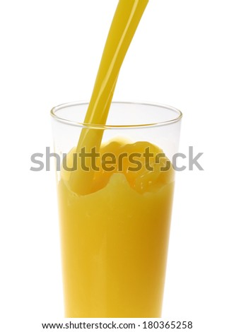 Orange juice pouring into tall glass on white background - stock photo