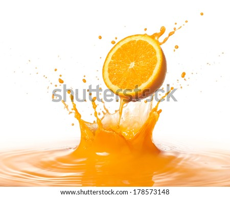 orange juice splashing with its fruit against white background - stock photo