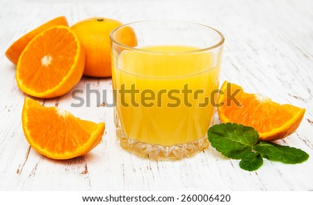 Orange juice with fresh fruits on a wooden background