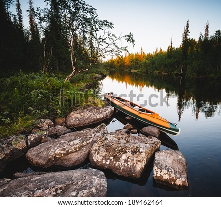 orange kayak on the shore of the purest northern river - stock photo