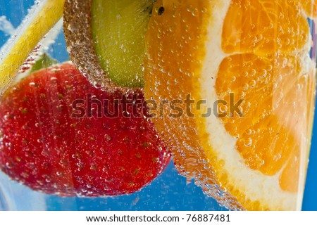 Orange, kiwifruit, lemon and strawberry cocktail - in soda water - against an ultramarine blue background - stock photo