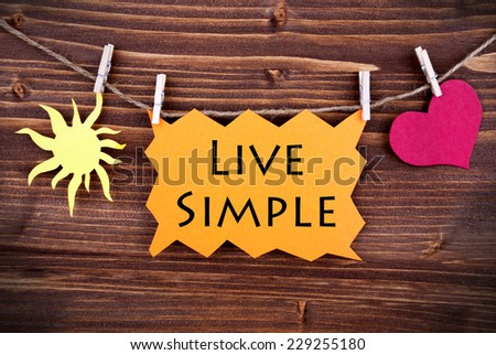 Orange Lable Saying Live Simple On Wooden Background Hanging On A Line, One Red Heart Symbol And One Yellow Sun Symbol Background Is Old Fashion - stock photo