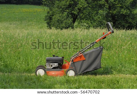 Orange lawn mower resting in backyard.