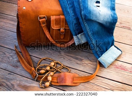 orange leather vintage suitcase travel bag, old fashioned beads and jeans on a wooden floor