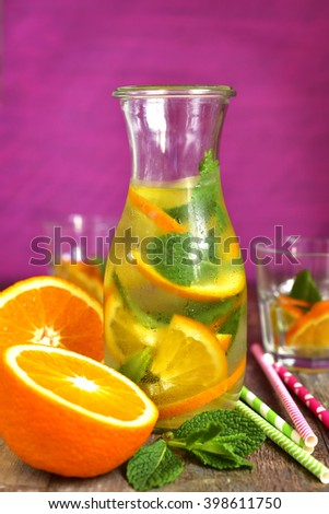 Orange lemonade in a bottle on a pink background.