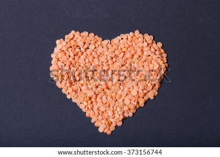 Orange lentils in a heart shape on a black background. - stock photo