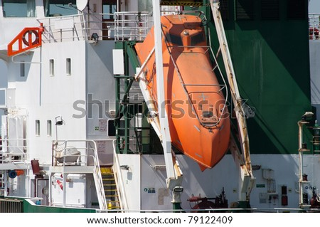 orange life boat docked to a large tanker - stock photo
