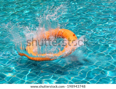 Orange life buoy is splashing with clear blue water in swimming pool, for the emergency case - stock photo