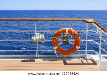 Orange Life buoy on the deck of a cruise ship. - stock photo