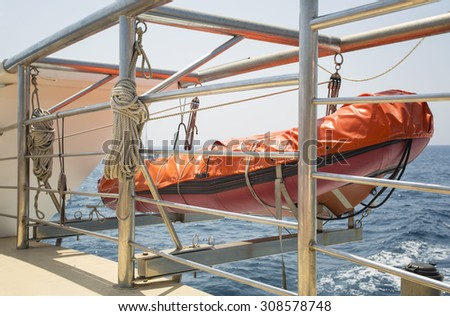 orange lifeboat hanging on ship at sea - stock photo