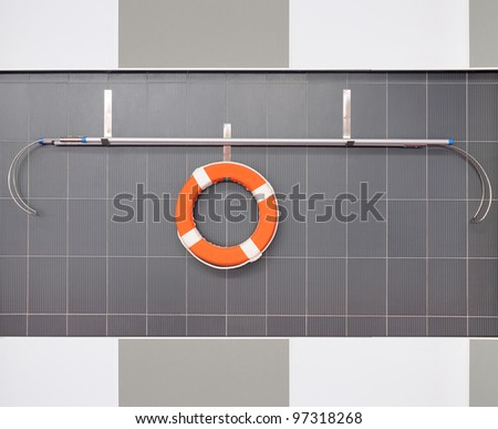 Orange lifebuoy hanging on a wall in pool - stock photo