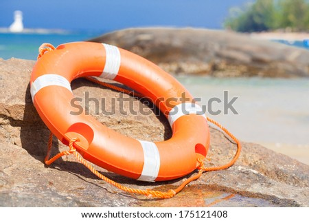 Orange lifebuoy on rocks at sea side. lifesaving equipment. concept - stock photo
