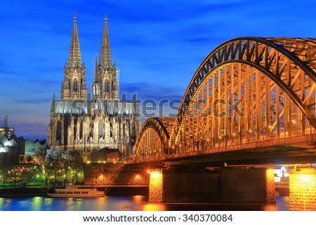 Orange light on the Hohenzollern bridge across Rhine river and Gothic Cathedral in Cologne, Germany - stock photo