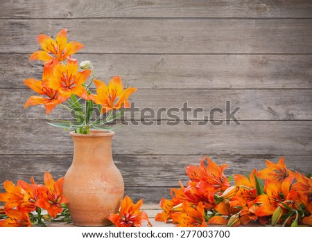 orange lily on wooden background - stock photo