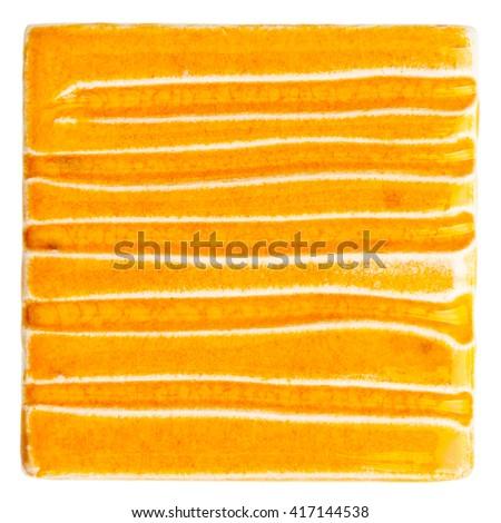Orange lined handmade glazed ceramic tile isolated on white background - stock photo