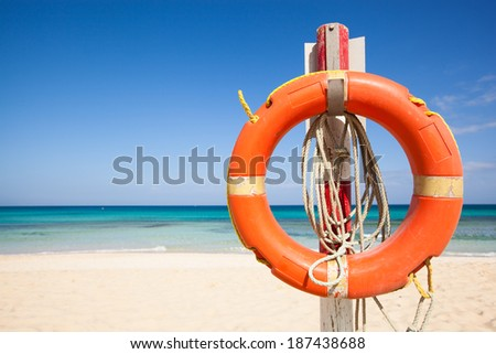 orange live saver attached at a wooden mast at the beach with a turquouise sea and a blue sky - stock photo