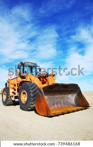 Orange loader bulldozer with cloud sky