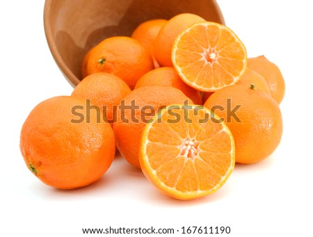 orange mandarines heap in wooden bowl on white  - stock photo