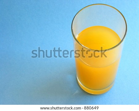 Orange, mango or other yellow fruit juice in a tall clear glass on blue background, space for text