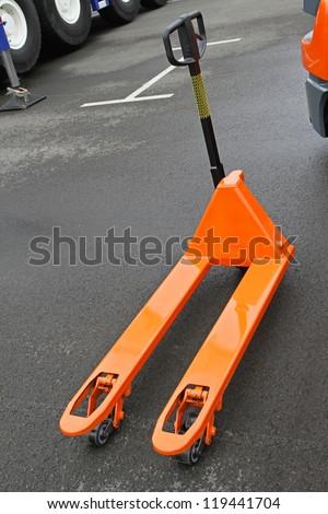 Orange manual pallet jack  truck for transport - stock photo