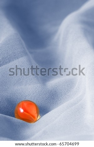 Orange marble against blue abstract background - stock photo
