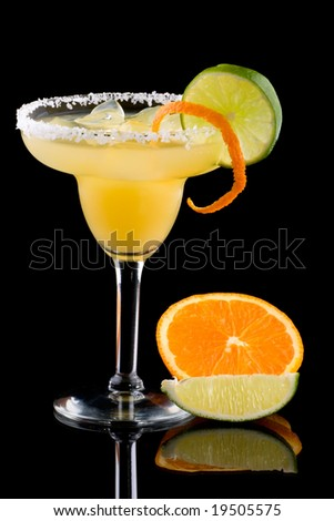 Orange Margarita in chilled glass over black background on reflection surface, garnished with fresh lime and orange. Most popular cocktails series.