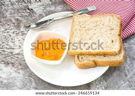 orange marmalade and bread for breakfast - stock photo